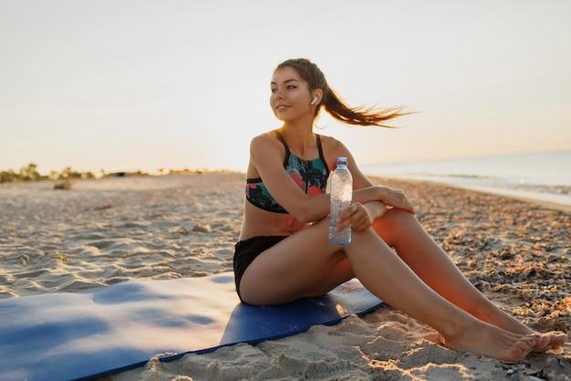 Trinkwasser der schönen fitnessathletenfrau nach dem training am sonnenuntergangabend im strand. stilvolle sportbekleidung.