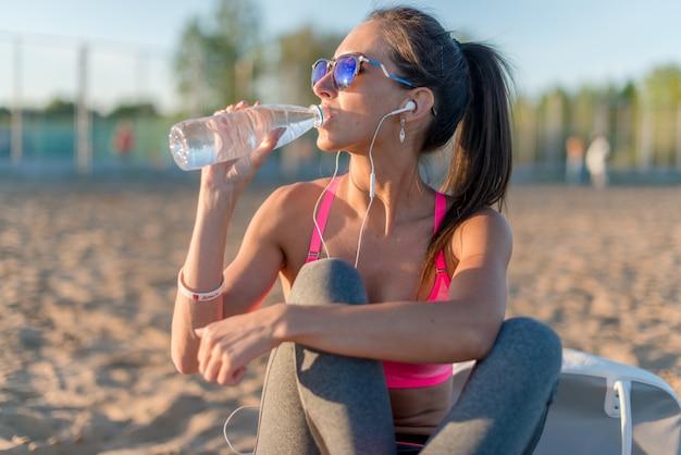 Trinkwasser der schönen fitnessathletenfrau nach dem training, das am sonnenuntergangabendabend im außenporträt des strandes ausübt.