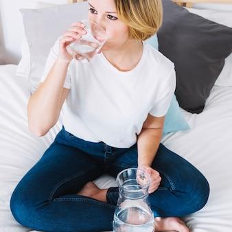 Trinkwasser der schönen frau auf bett