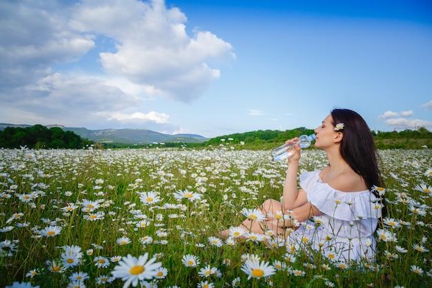 Trinkwasser der schönen frau auf einem feld mit gänseblümchen