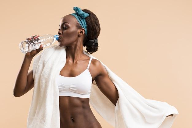 Trinkwasser der sportlichen frau von der flasche