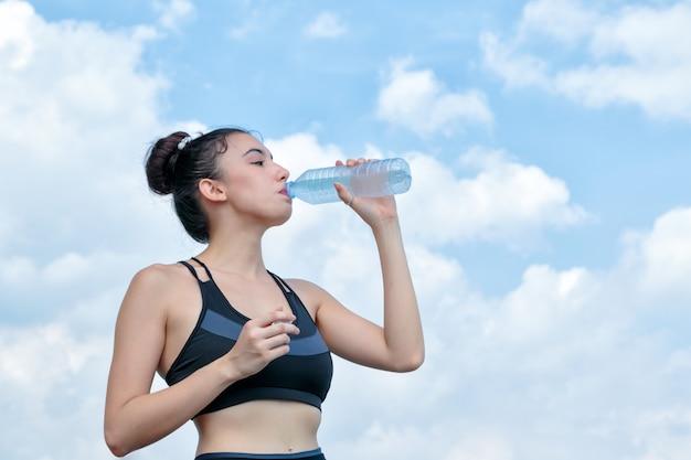 Trinkwasser der yoga athletenfrau nach trainieren heraus