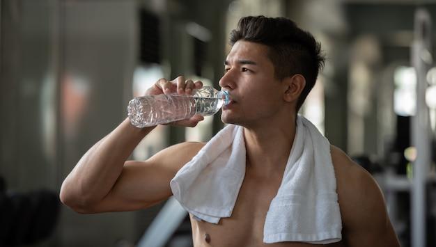 Trinkwasser des bodybuildermannes, nachdem gewichte in der sportturnhalle, abschluss oben angehoben worden sind.