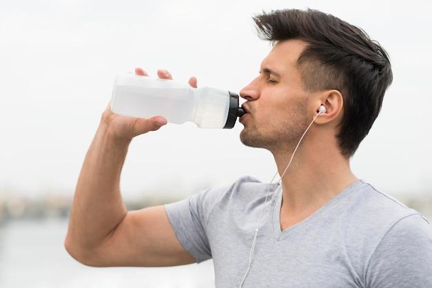 Trinkwasser des erwachsenen mannes der seitenansicht