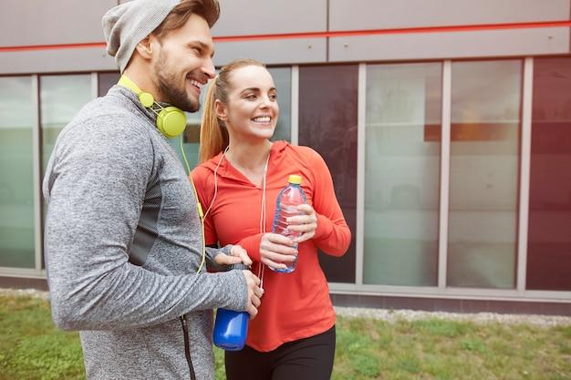 Trinkwasser des glücklichen paares nach dem training