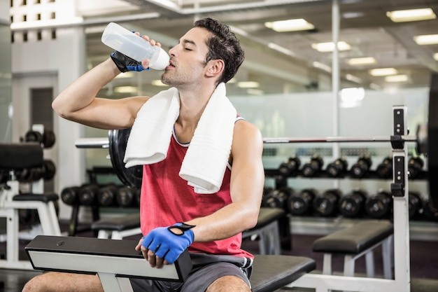 Trinkwasser des gutaussehenden mannes beim sitzen auf bank in der turnhalle