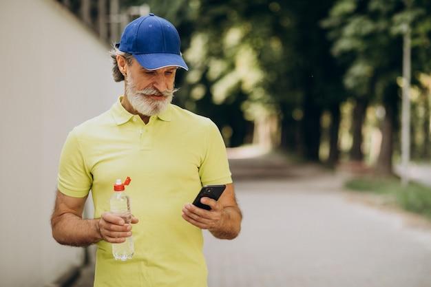 Trinkwasser des hübschen mannes im park nach dem joggen
