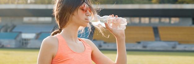 Trinkwasser des jugendlichen des jungen mädchens von der flasche nachdem dem laufen