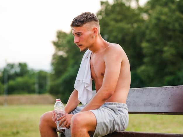 Trinkwasser des jungen attraktiven sportlers nach dem training - sportkonzept
