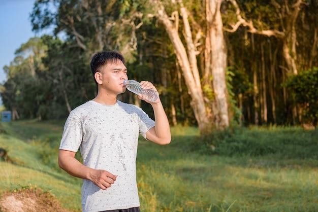 Trinkwasser des jungen mannes nachdem dem laufen