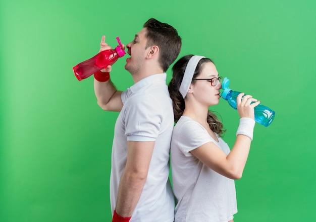 Trinkwasser des jungen sportlichen paares nach dem training über grün