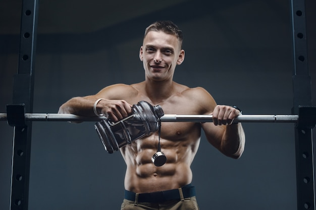 Trinkwasser des kaukasischen fitnessmannes nach dem training im fitnessstudio.