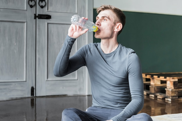 Trinkwasser des mannes von der flasche, die auf boden sitzt
