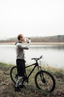 Trinkwasser des radfahrers von der flasche, die nahe dem see steht
