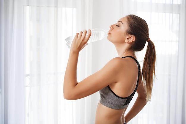 Trinkwasser des schönen fitnessmädchens von einer plastikflasche