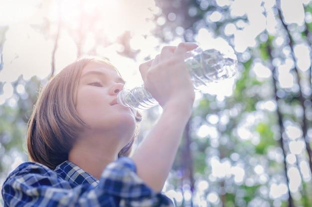 Trinkwasser des schönen mädchens von der plastikflasche mit sonnenaufgang