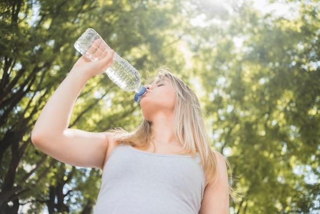Trinkwasser des sportlichen mädchens der ansicht von unten