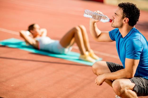Trinkwasser des sportlichen mannes während junge frau, die übung im hintergrund tut