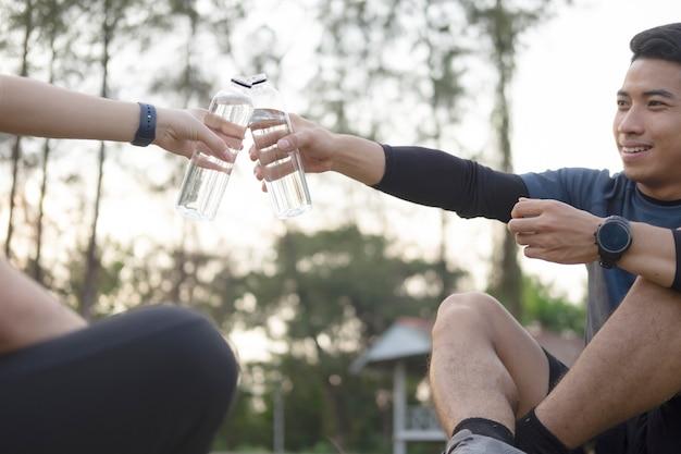 Trinkwasser des sportpaares des jungen paares nach dem training.