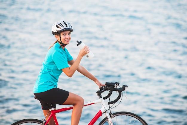 Trinkwasser des weiblichen radfahrers mit meer