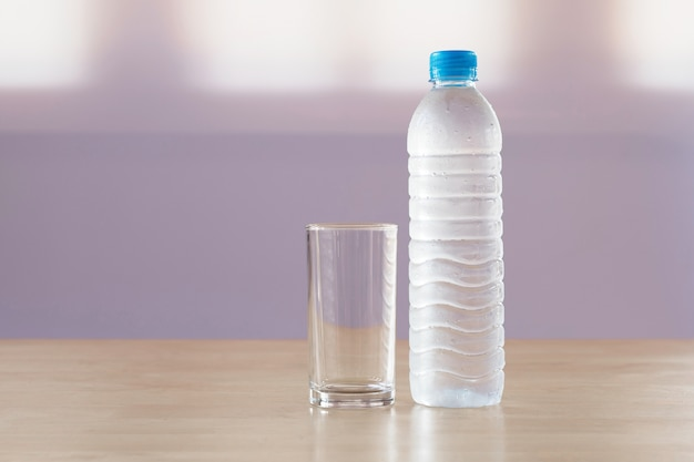 Trinkwasser in der plastikflasche mit glas auf tabelle