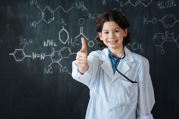 Tritt meinem team bei. amüsiert lächelnder optimistischer teenager, der nahe an der tafel in der schule steht, während er medizinischen unterricht genießt und daumen zeigt