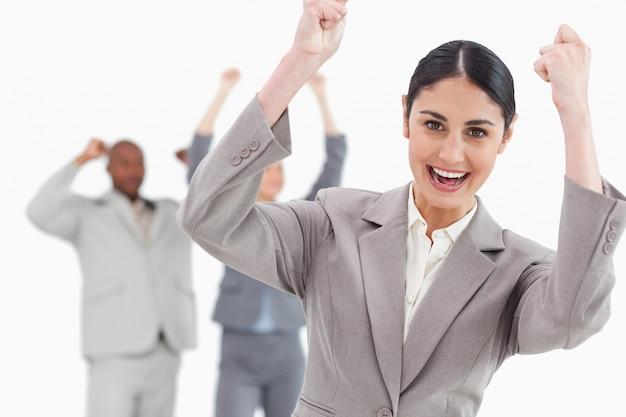 Triumphierende geschäftsfrau mit zujubelnden mitarbeitern hinter ihr