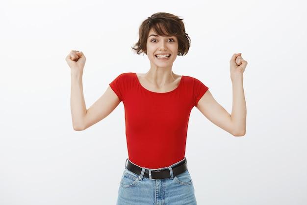 Triumphierende glückliche frau, die hände in hurra hebt, sich über geste freut und sieg feiert