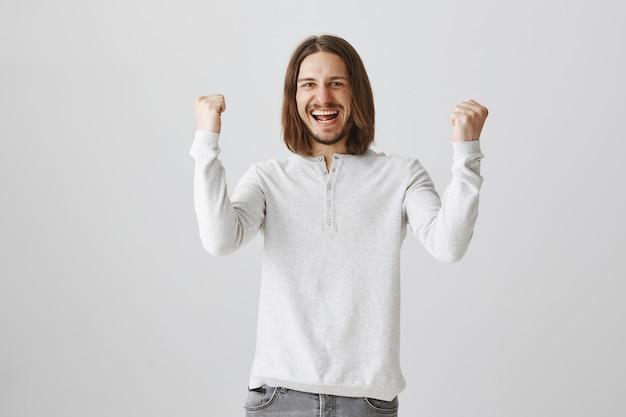 Triumphierender fröhlicher bärtiger mann faustpumpe, der den sieg feiert