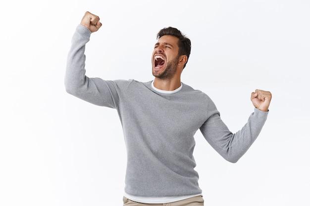 Triumphierender junger hispanischer typ, der sich wie weltmeister fühlt, erfolg oder sieg feiert, ja als zielwettbewerb schreit, sieg erringt oder wünschenswert, faustpumpe ermutigt und motiviert