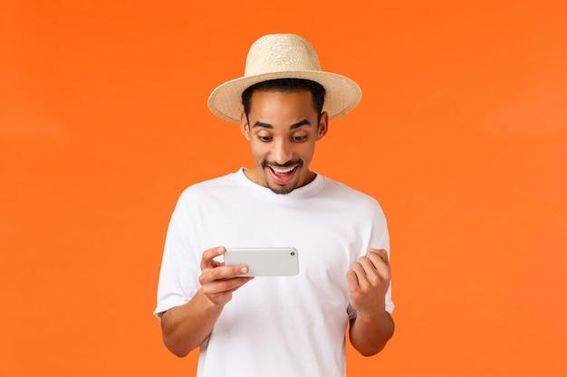 Triumphierendes glückliches, nettes gewinnendes rennen des afroamerikanermannes, geführtes hartes levelspiel, faustpumpe sagen ja und das lächeln zufrieden gestellt und halten smartphone horizontal, orange
