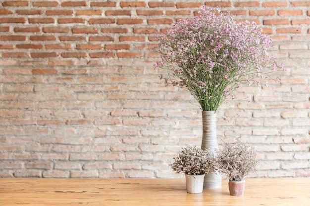 Trockenblume auf hölzerner tabelle mit backsteinmauerhintergrund