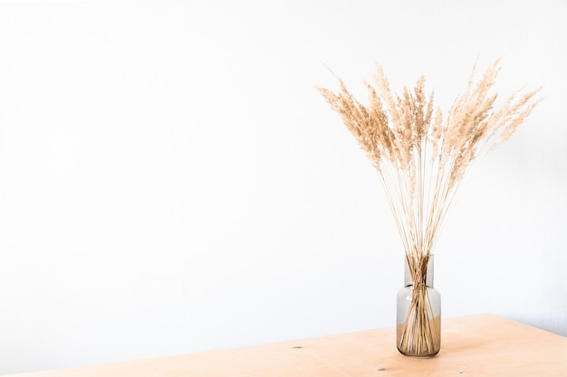 Trockenblumen in einer glasvase mit einer leeren lichtwand