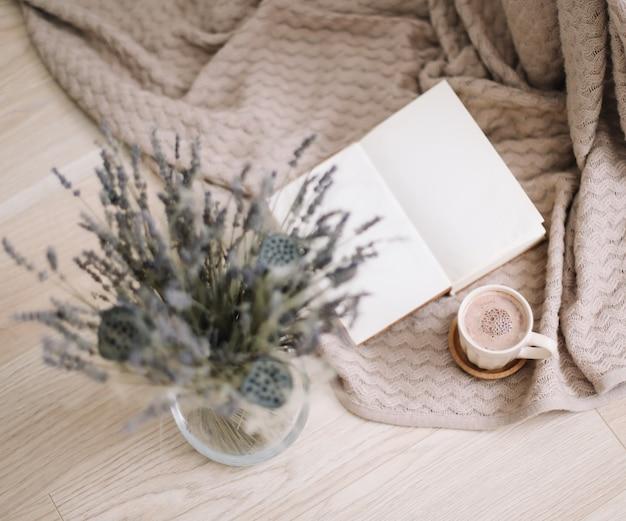 Trockenblumen und eine tasse cappuccino mit buch auf hölzernem hintergrund. draufsicht. flatlay