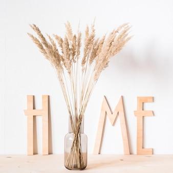 Trockenblumen und holzbuchstaben nach hause auf dem hintergrund einer hellen wand Premium Fotos
