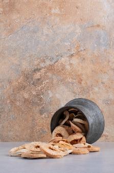 Trockene apfelscheiben in einer metallischen ethnischen tasse.