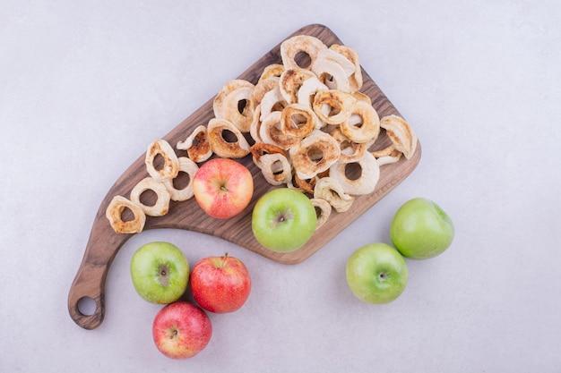 Trockene apfelscheiben mit frischen äpfeln auf holzbrett auf grau.
