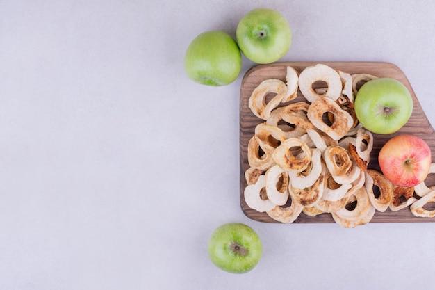 Trockene apfelscheiben mit ganzen äpfeln in einer holzplatte