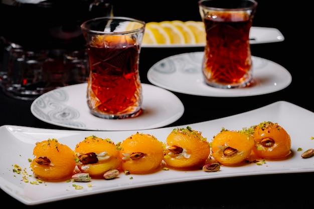 Trockene aprikose mit mandelpistaziencreme innerhalb des tees in armudy zitronenseitenansicht