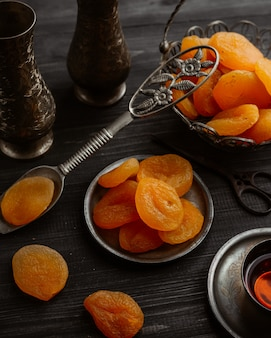 Trockene aprikosenfrüchte innerhalb der metallischen schalen und des löffels.