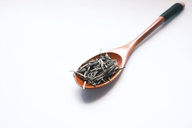 Trockene blätter des grünen tees auf löffel auf weiß