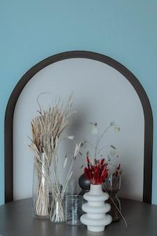 Trockene blumen in vasen stehen auf einem holztisch gegen die blaue wand mit bogen herbst dekorative komposition vertikal