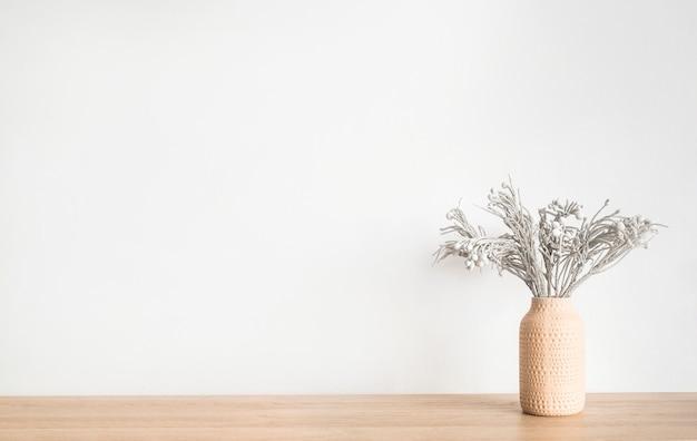 Trockene blumen pflanzen blumen in einem vasentisch gegen weiße wand minimalistisch skandinavisch