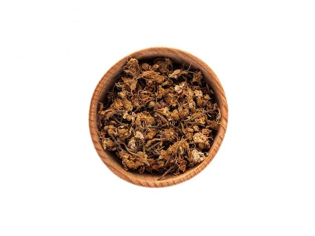 Trockene blumen von castanea oder von kastanie in einer hölzernen schale auf einer weißen tabelle