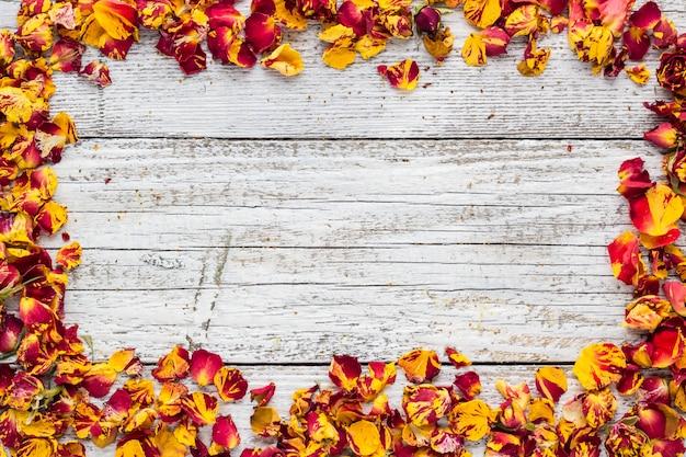 Trockene blumenblätter von stiegen auf ein weißes holz