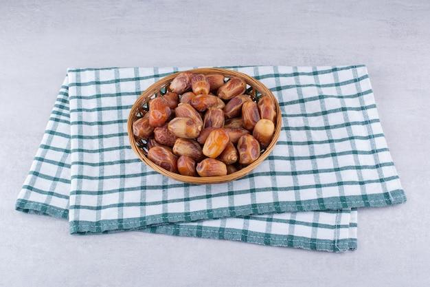 Trockene braune datteln in einer holzplatte. foto in hoher qualität