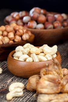 Trockene cashewnüsse, haselnüsse und andere trockenfrüchte auf einem alten holztisch