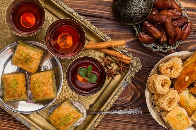 Trockene datteln auf untertasse in der nähe von tassen tee und türkischen desserts auf tablett