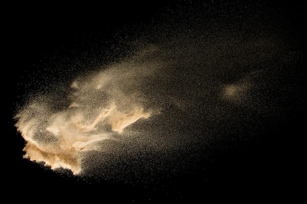 Trockene flusssandexplosion lokalisiert auf schwarzem hintergrund. abstrakte sandwolke. braunes farbiges sandspritzen gegen dunklen hintergrund.