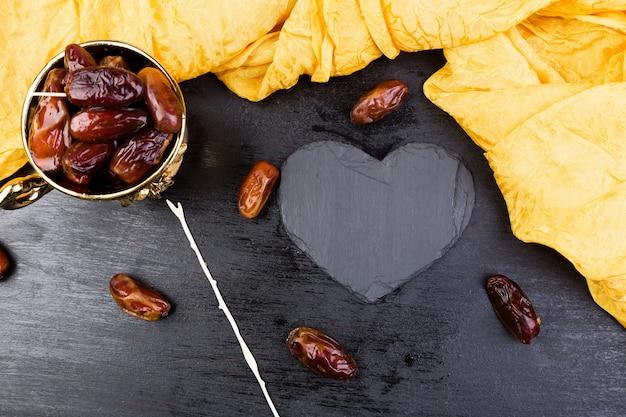 Trockene fruchtdaten in der goldenen schale nahe schwarzem herzen des schiefers.